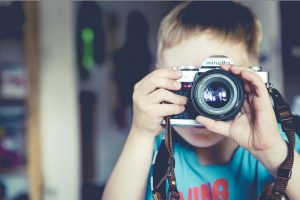 Kid taking photo with camera.